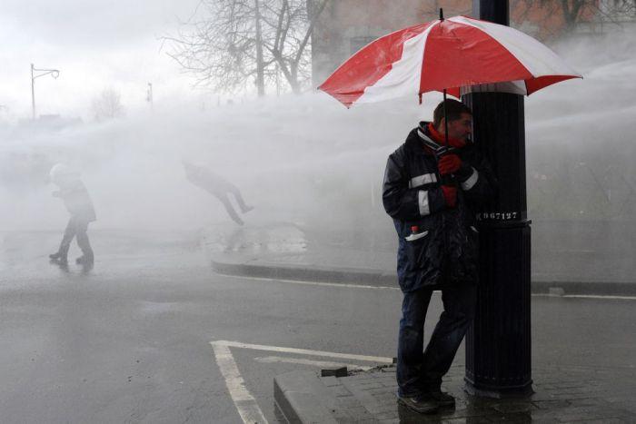 Protestas de trabajadores de ArcelorMittal que son golpeados con un cañón de agua en Namur (sur de Bélgica), 20 de marzo de 2013.JOHN THYS (AFP)
