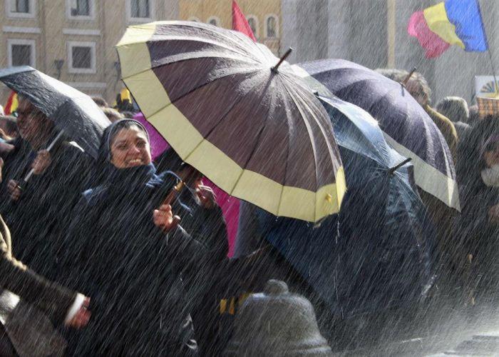 Una monja se protege de las salpicaduras de agua de una fuente en la Plaza de San Pedro en el Vaticano, el 24 de febrero de 2013.ERIC GAILLARD (REUTERS)