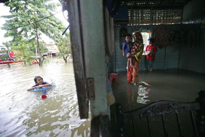 Una niña nada en el exterior de su vivienda inundada en Rantau Panjang, un pueblo malasio frontera con Tailandia, a 500 km al noreste de Kuala Lumpur, diciembre 2012.(REUTERS)