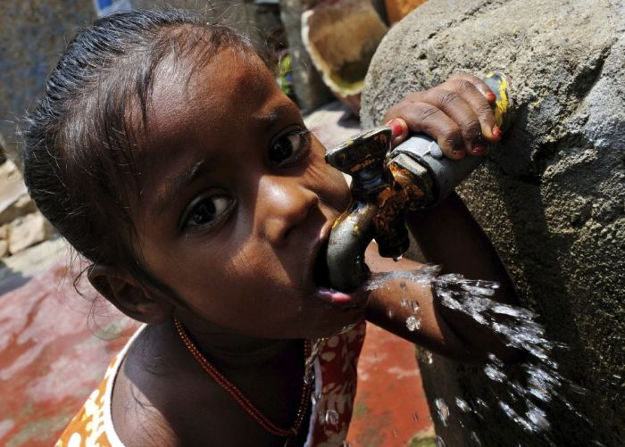 Una niña bebe agua de una fuente en Bangalore (India), 22 de marzo de 2013.Jagadeesh Nv (EFE)