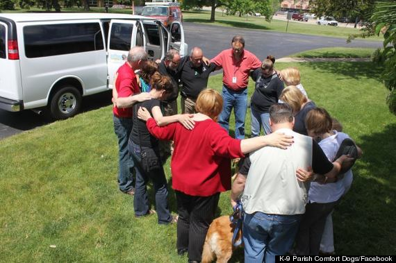 Lutheran Church Charities staff and volunteers pray before their comfort dogs depart for Oklahoma on Tuesday in Addison, Ill. (via Facebook)