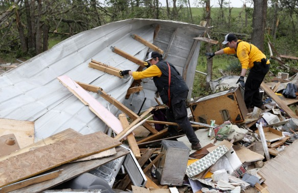 Members of the Chickasaw Nation search and rescue group dig through debris, Monday, May 20, 2013, to locate a kitten buried in the rubble of a mobile home destroyed in Sunday's tornado, in the Steelman Estates Mobile Home Park, near Shawnee, Okla. (AP Photo Sue Ogrocki)